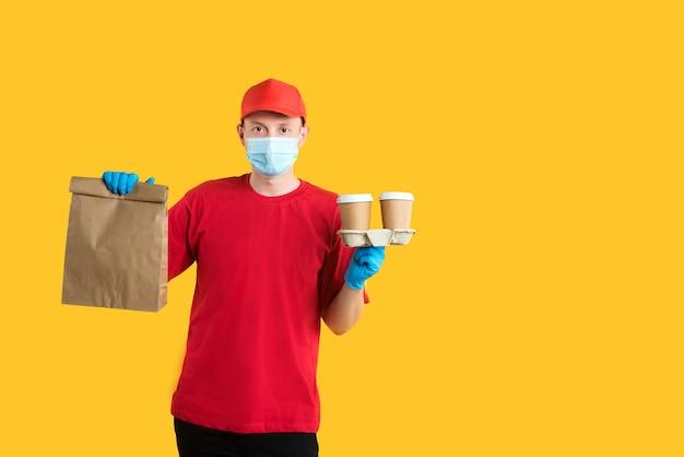 Koerier in rood uniform in masker en handschoenen houdt ambachtelijke eco-pakket en drankjes op geel