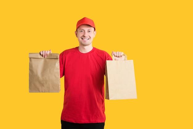 Koerier in rood uniform met ambachtelijke tassen geeft fastfoodbestelling op geel