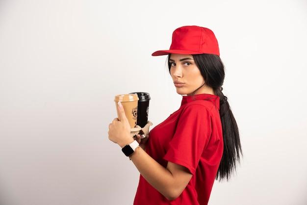 Koerier in rood uniform met twee kopjes koffie. hoge kwaliteit foto