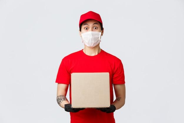 Koerier in rood uniform pet en t-shirt, met doos met bestelling van de klant, met medisch masker en beschermende handschoenen voor de veiligheid tijdens pandemisch coronavirus. bezorger brengt uw bestelling