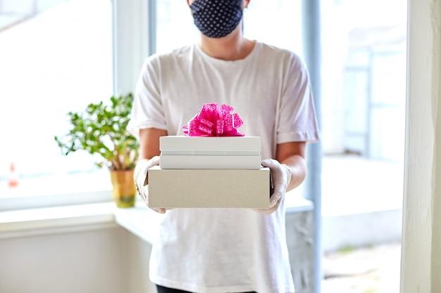 Koerier man contactloze levering presenteert, geschenkdoos tijdens een coronavirus-epidemie.