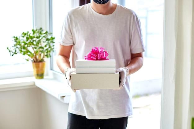 Koerier man in het wit met bescherming medische masker en handschoenen contactloze levering presenteert, geschenkdoos