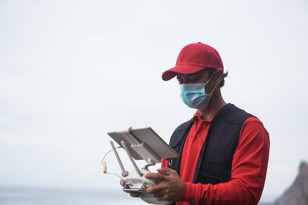 Koerier man vliegende doos voor levering met drone terwijl hij veiligheidsmasker draagt