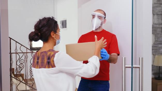 Koerier met beschermingsmasker die pakket aan klant levert.