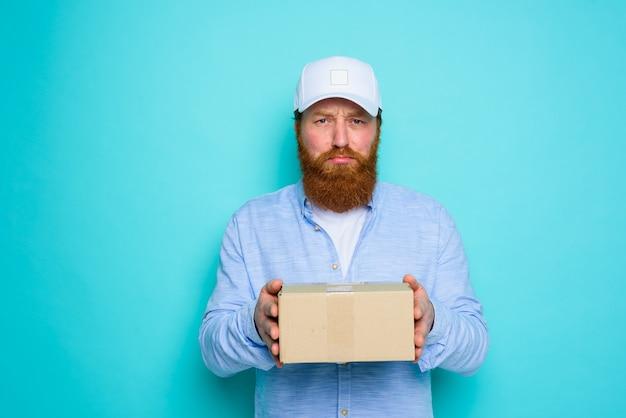 Koerier met hoed is niet tevreden met het bezorgen van een kartonnen doos