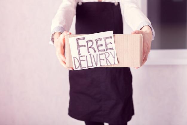 Koerier met in haar handen een kartonnen doos met het opschrift