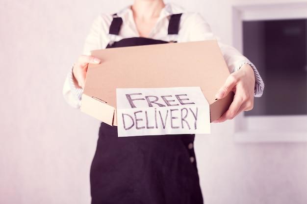 Koerier met in haar handen een kartonnen doos pizza met het opschrift