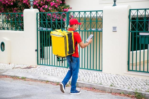 Koerier met isotherme voedselrugzak raadplegenstablet, adres controleren en naar poort en deurbel lopen. communicatie- of bezorgserviceconcept