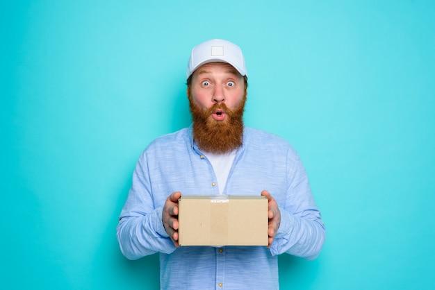 Koerier met kartonnen doos in de hand is ergens verbaasd over