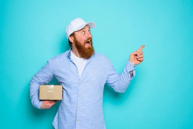 Koerier met kartonnen doos in de hand is verrast en geeft iets aan