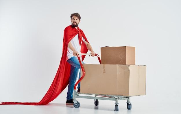 Koerier met kartonnen dozen in vrachtkar en rode superheldmantel