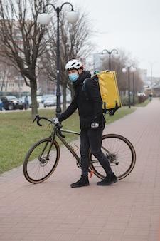 Koerier met medisch gezichtsmasker en thermo rugzak, wandelen in de stad met zijn fiets