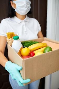 Koerier met verpakkingsdoos met eten, contactloze levering, service quarantaine pandemie coronavirus, vrijwillige vrouw in wit beschermend masker en handschoenen levering donatiebox thuis.