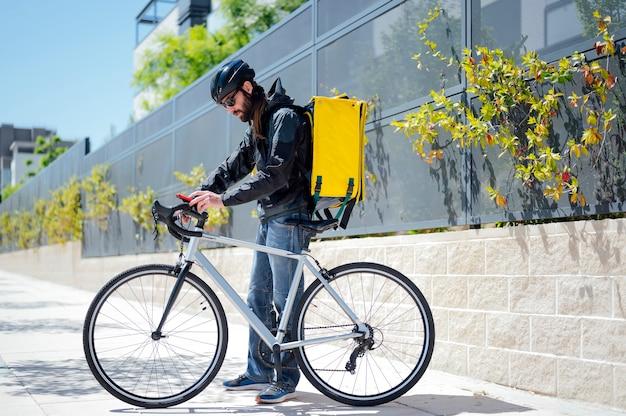 Koerier op fiets die voedsel in de stad bezorgt met behulp van smartphone