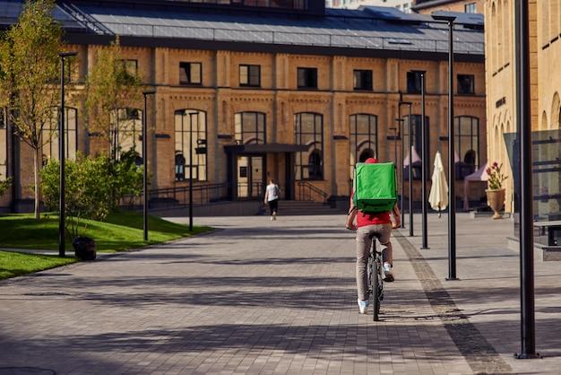 Koerier op fietstocht langs mooie zonnige straat