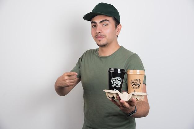 Koerier wijzend op afhaalmaaltijden kopjes koffie op witte achtergrond.