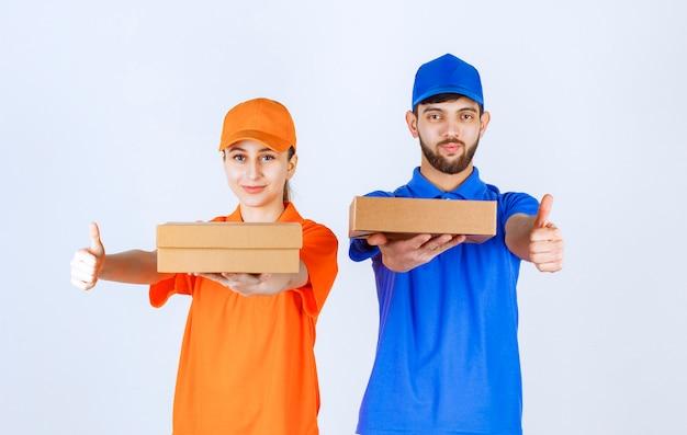 Koerierjongen en -meisje in blauwe en gele uniformen die kartonnen afhaaldozen en winkelpakketten houden en tevredenheid handteken tonen.