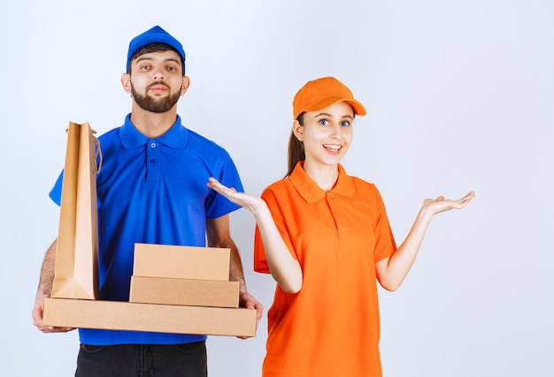 Koerierjongen en -meisje in blauwe en gele uniformen die kartonnen afhaaldozen en winkelpakketten houden.