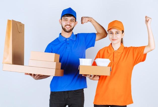 Koerierjongen en -meisje in blauwe en gele uniformen die kartonnen afhaaldozen en winkelpakketten vasthouden en hun vuisten tonen.