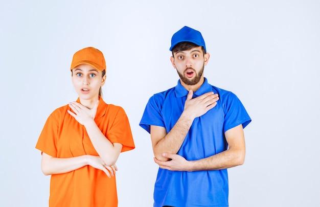 Koerierjongen en -meisje in blauwe en gele uniformen die zelf wijzen en emotioneel voelen.