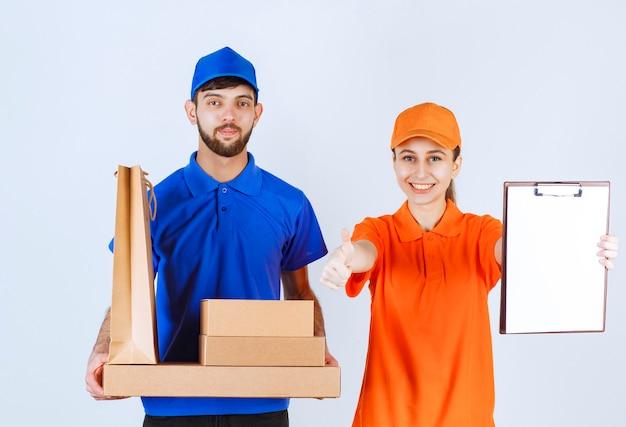 Koerierjongen en -meisje in blauwe en gele uniformen met kartonnen afhaaldozen en winkelpakketten, handtekeninglijst presenteren en zich tevreden voelen.