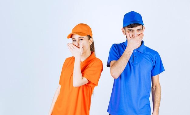 Koerierjongen en -meisje in blauwe en gele uniformen voelen zich moe en slaperig.
