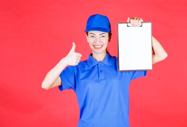 Koeriersmeisje in blauw uniform dat een takenlijst vasthoudt en een teken van plezier toont.