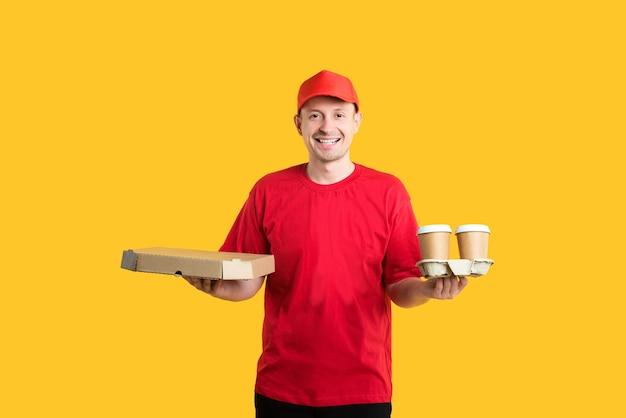 Koeriersmens in rode pet en t-shirt houdt dozen en koffie op geel