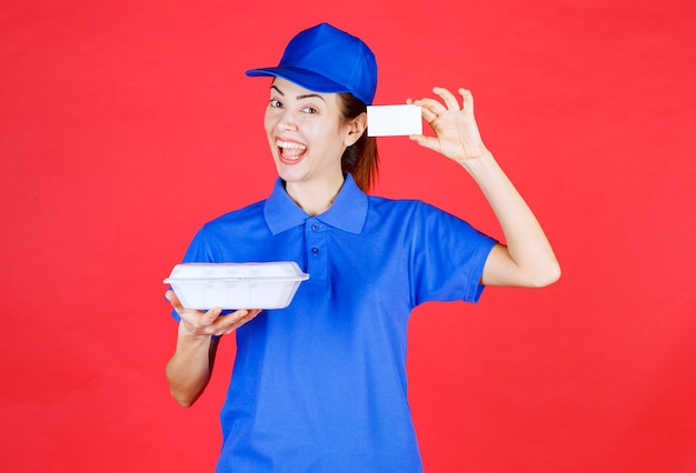 Koeriersvrouw die een witte afhaalmaaltijdendoos houdt en haar visitekaartje voorstelt.