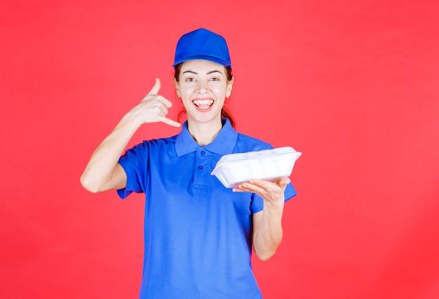 Koeriersvrouw in blauw uniform die een witte afhaalmaaltijden vasthoudt en om een telefoontje vraagt.
