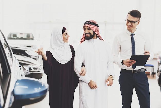 Koeweit man koopt auto voor vrouw happy dealer smiles.