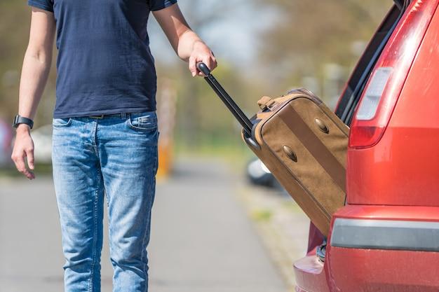 Koffer in de hand, trok de jonge man uit de auto van de kofferbak