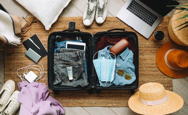 Koffer inpakken voor reisvakantie in nieuw normaal bovenaanzicht.