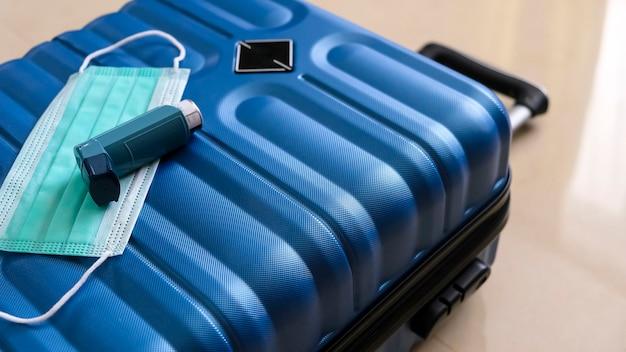 Koffer, masker en inhalator compleet voor reizen tijdens de covid pandemie. conceptvakanties en reizen. kopieer ruimte, selectieve aandacht. ondiepe scherptediepte