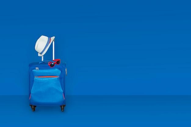 Koffer met een zomerhoed en zonnebril bij het stemmen in klassieke blauwe kleurenmuur.