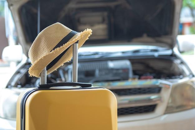 Koffer met hoed en auto, voorbereiden of controleren van uw auto voordat een road trips concept