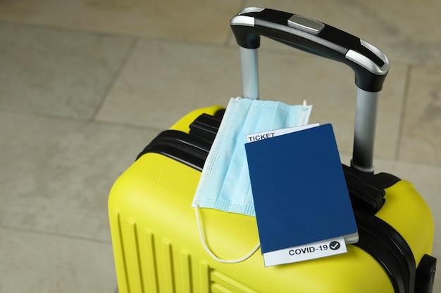 Koffer met masker en paspoort met kaartje en covid - 19 mark