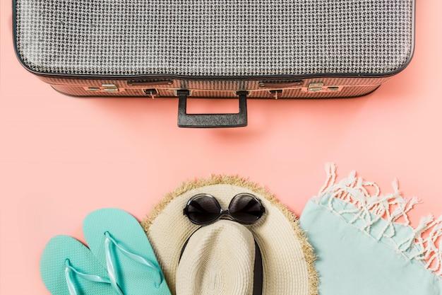 Koffer met vrouwelijke outfit voor strand op roze. bovenaanzicht met kopie ruimte.