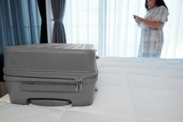 Koffer op bed in hotelkamer en jonge vrouw die overschrijving bestelt via mobiele applicatie,