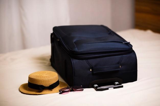Koffer reistas en strooien hoeden liggen op het bed in de hotelkamer inchecken bij de hoteltransfer en reis naar de zee rest