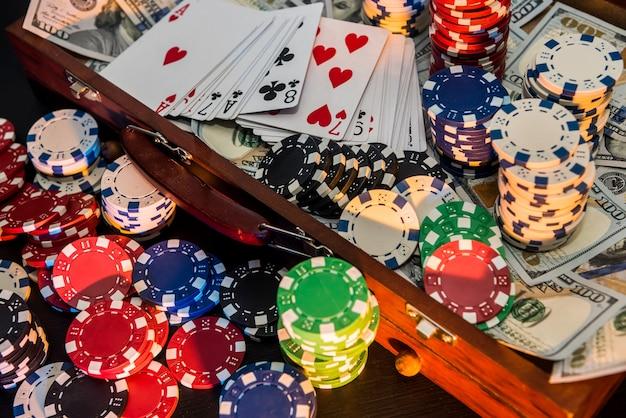 Koffer vol chips, dollars en speelkaarten op een zwarte achtergrond