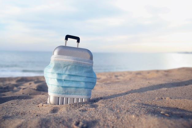 Koffer voor reizen met een medisch masker op het strand