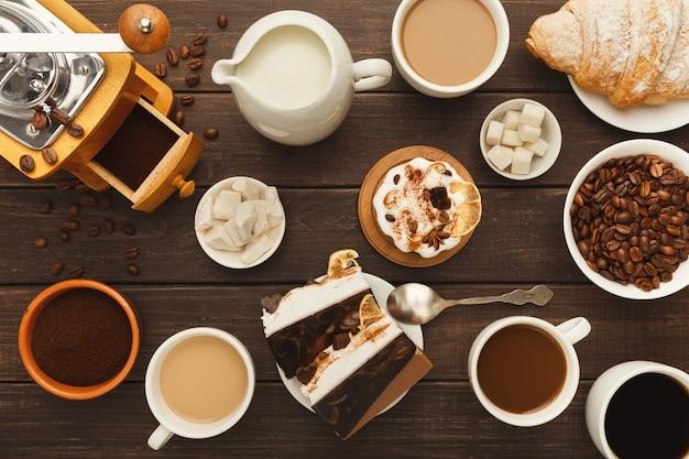 Koffie achtergrond. bovenaanzicht op kopjes van verschillende soorten koffie, gemalen bonen, melk, vintage grinder en zoete desserts op rustieke houten tafel