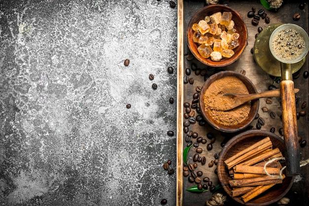 Koffie achtergrond gelaste koffie in een turks met suiker, kaneel en koffiebonen op een rustieke achtergrond