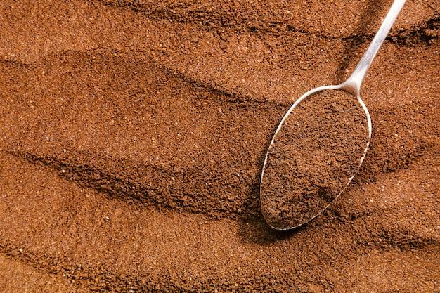 Koffie achtergrond. gemalen koffie in lepel op koffie achtergrond.