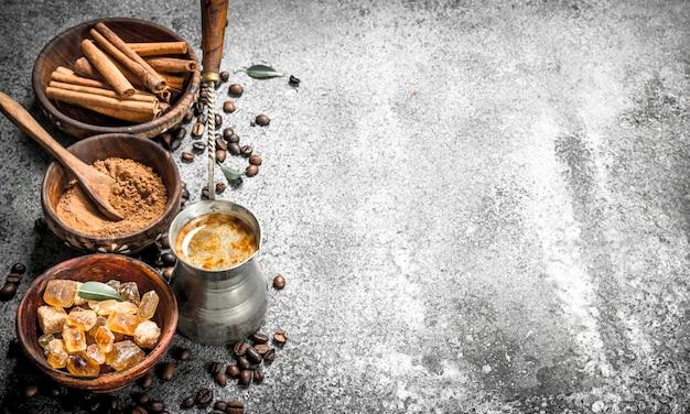Koffie achtergrond koffie in turkije met kristallen van suiker, kaneel en gemalen koffie op een rustieke achtergrond
