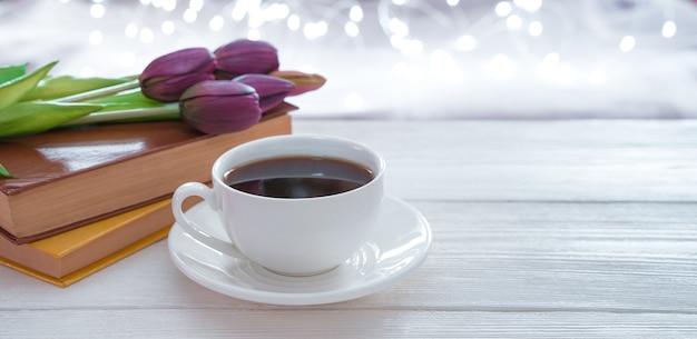 Koffie, boeken en bloemen op een lichte achtergrond met gloeiende slingers. zijaanzicht met kopie ruimte