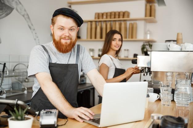 Koffie business concept - jonge knappe bearded bartende, barista of manager werken en plannen in laptop op de moderne koffie winkel.
