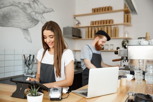 Koffie business concept - mooie kaukasische barman barista of manager postorder in digitale tablet menu bij moderne koffie winkel.
