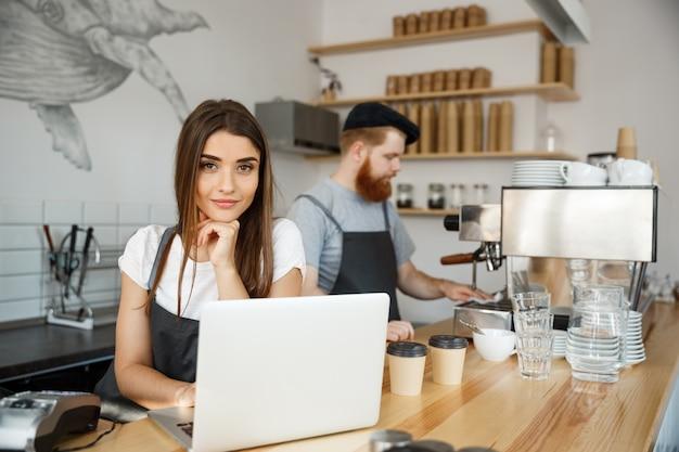 Koffie business concept - mooie kaukasische barman barista of manager werken en plannen in laptop op moderne koffie winkel.